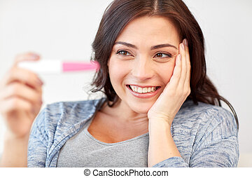 happy woman looking at home pregnancy test - pregnancy,...