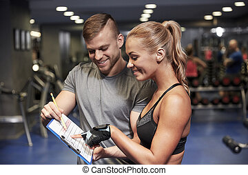smiling woman with trainer and clipboard in gym - fitness,...