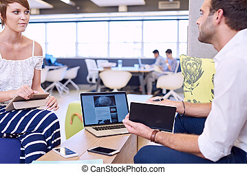 Woman holding tablet while paying attention to male business...