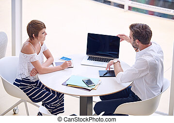 Man opening laptop while seated at table with woman -...