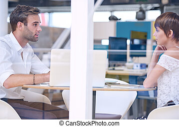 Mentor busy tutoring his female student in co-work space