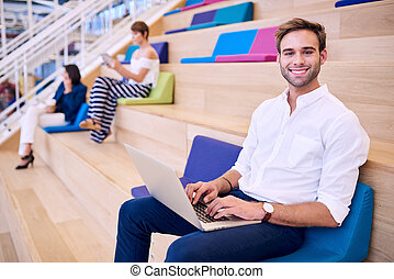 Man working on ultrabook in bright colourful co work space -...