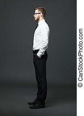Fullbody profile view of handsome businessman on dark gray...