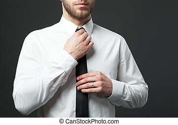 Mid section of young fit businessman adjusting tie isolated...