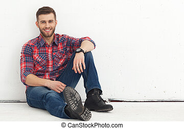 Portrait of happy handsome young man against white wall -...