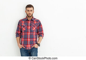 Handsome young guy standing against white wall - Portrait of...
