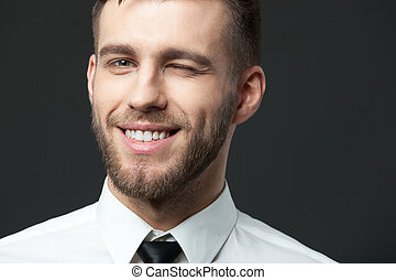 Studio portrait of handsome young businessman smiling and...