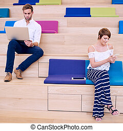Woman texting on phone and man browsing with modern notebook...