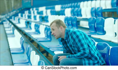 Guy drinking from the bottle on the stadium tribune - Young...
