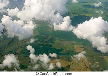 Aircraft bird view of green fields white clouds
