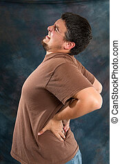 Man Back Pain - Man with back pain massages his back trying...