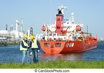 Harbor Workers - Two harbor workers at a petrochemical...