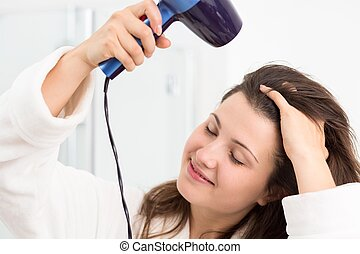 Woman with hairdryer - Young woman drying hair with hair...