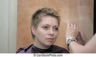 Hairdresser arranges and styles short hair blond