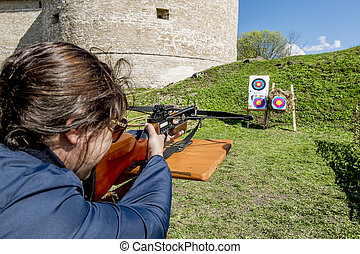 Girl shoots a crossbow from the walls of the fortress in...
