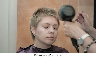 Hairdresser dries and styles short hair blond head -...