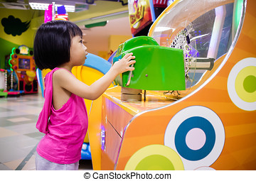 Asian Little Chinese Girl Playing Arcade Game Machine at a...