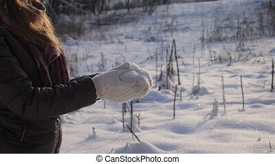 Happy young woman playing with snow
