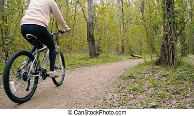 girl rides a bicycle on a footpath in the woods