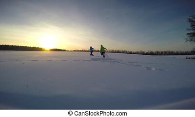 Young couple playing outdoors in the snow on sunset