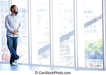 Full body shot of man with beard looking out window