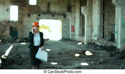 architect builder engineer builder of ruined building looking girl work plan for the construction site construction plan explains in helmet construction helmet girl looks architectural plan and construction plans to repair the area