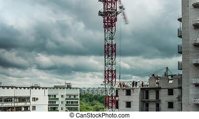 workers on the building construction with cloudy sky and...