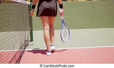 Athletic young woman tennis player walking away from the...