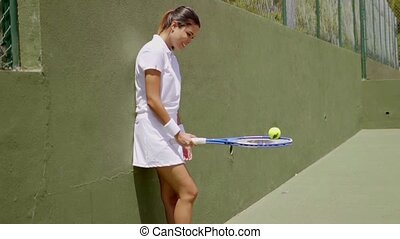 Pretty athlete practicing with ball and racket in green...