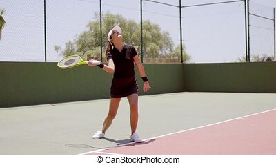 Attractive female tennis player wearing black skirt and top...