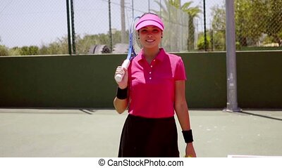 Attractive woman player walking on a tennis court