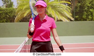 Attractive athlete poses near net in tennis court while...