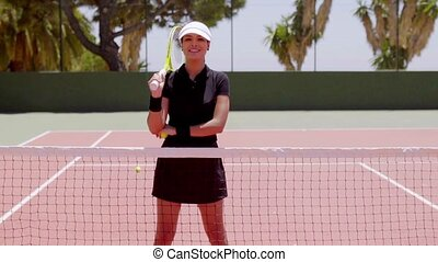 Tennis player at net ready to serve ball - Single smiling...