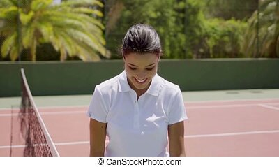 Pretty female tennis player with racket and ball while...