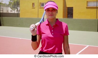 Attractive woman player walking on a tennis court...