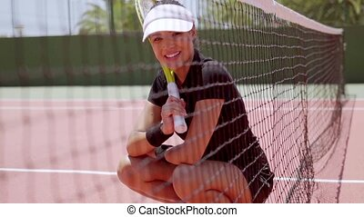 Smiling young tennis player crouching near the net - Smiling...