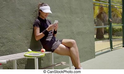 Attractive young tennis player checking her mobile -...