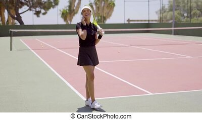 Woman talking on phone at tennis court - Single woman in...