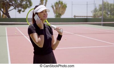 Laughing tennis player on phone at court in summer -...