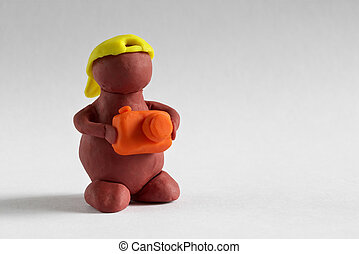 Plasticine man with photo camera over grey background