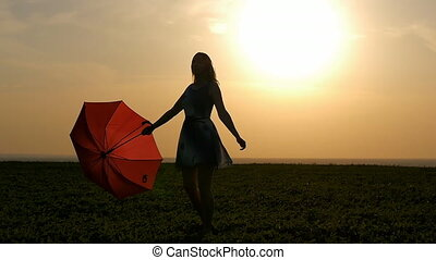 portrait of a beautiful girl with a red umbrella in the sunset smiling emotions green grass field smiling girl dancing laughing spinning golden hour sunset silhouette of a slender girl