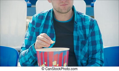 Young man eating popcorn at the stadium - Man with great...