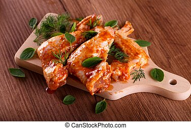 Three marinated chicken wings on wooden board