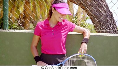 Relaxed confident young woman tennis player leaning on the...