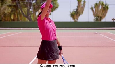 Smiling victorious young woman tennis player raising her...