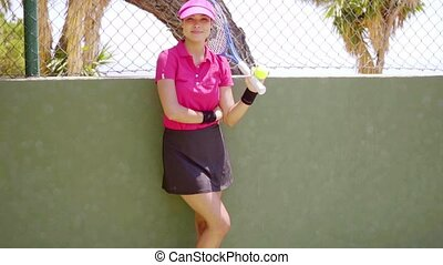 Woman in tennis outfit relaxes against wall with fence atop...