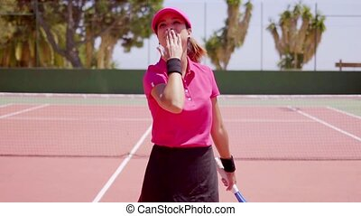Female athlete makes gesture with her arm while wearing pink...