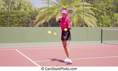 Woman juggling tennis balls on court - Single woman in pink...