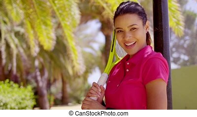 Gorgeous young woman tennis player in the tropics standing...