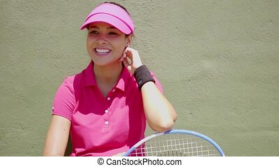 Laughing tennis player holding racket on her knees